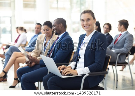 Side view of Caucasian female executive using laptop in conference room, smiling to camera. With executives in the background. #1439528171