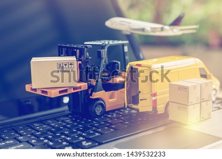 Logistics, supply chain and delivery service concept : Fork-lift truck moves a pallet with box carton. Van on a laptop computer, depicts wide spread of products around globe in ecommerce booming era #1439532233