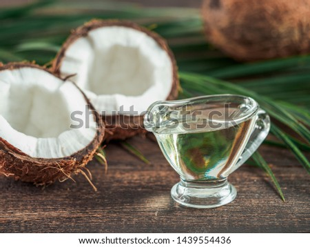 Liquid coconut MCT oil and halved coco-nut on wooden table. Health Benefits of MCT Oil. MCT or medium-chain triglycerides, form of saturated fatty acid. #1439554436
