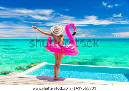 Vacation woman in bikini with inflatable pink flamingo float pool toy mattress by swimming pool. Elegant lady relaxing sunbathing enjoying travel holidays at resort pool. Luxury lifestyle travel, #1439565983