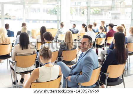 Side view of mature Caucasian male executive sat in conference room, smiling to camera #1439576969