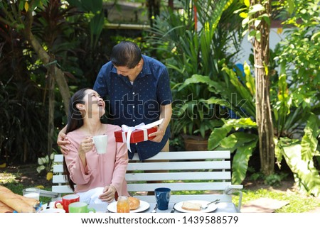asian elderly couple with blue and pink shirt sitting at a breakfast table in backyard outdoor on wedding anniversary day. Asian elder husband giving surprise gifts to his asian elder wife with smile #1439588579