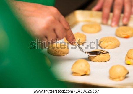 Fork Pressing Cookie Dough on a Tray #1439626367