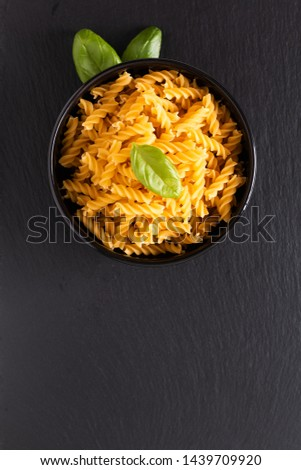 Food concept raw organic Italian Fusili pasta in black bowl on black slate board with copy space #1439709920