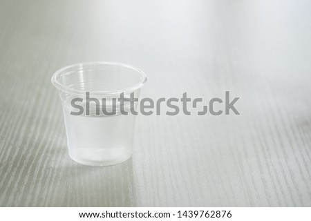 Drinking water in a clear glass on a white table #1439762876