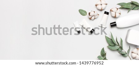 Cosmetics SPA branding mock-up. White cosmetic bottle containers with cotton flowers, eucalyptus twigs on gray background top view flat lay. Natural organic beauty product concept, Minimalism style #1439776952