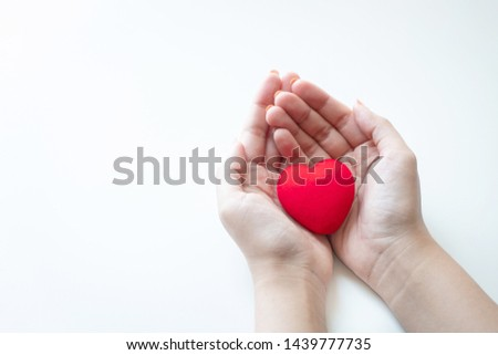 Female hands holding a red heart #1439777735