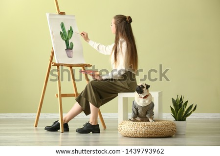 Teenage artist with cute pug dog at home