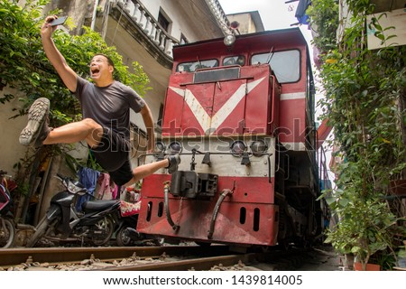 Man with mobile phone makes dangerously selfie photo in front of moving train. An undisciplined tourist in the popular Hanoi railway street, Vietnam. Royalty-Free Stock Photo #1439814005
