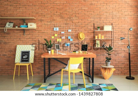 Workplace with mood board near brick wall in modern room