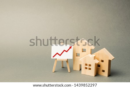 three wooden houses and a red up arrow on the sign. Real estate value increase. High rates of construction, high liquidity. Supply and demand. Rising prices for housing, building maintenance. #1439852297