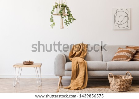 Modern boho interior of living room at cozy apartment with gray sofa, honey yellow pillows and plaid, plants, paintings, rattan basket and design personal accessories. Stylish home decor. Template. #1439856575