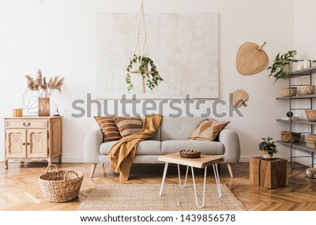 The stylish boho compostion at living room interior with design gray sofa, wooden coffee table, commode and elegant personal accessories. Honey yellow pillow and plaid. Cozy apartment. Home decor #1439856578