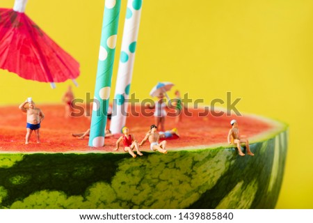 some miniature people wearing swimsuit relaxing on a refreshing ripe watermelon, with some white and blue drinking straws and a paper umbrella stuck in it, against a yellow background Royalty-Free Stock Photo #1439885840