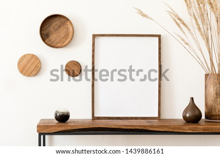Design scandinavian interior of living room with wooden console, rings on the wall, mock up poster frame, flowers in vase and elegant personal accessories. Modern home decor. Template.