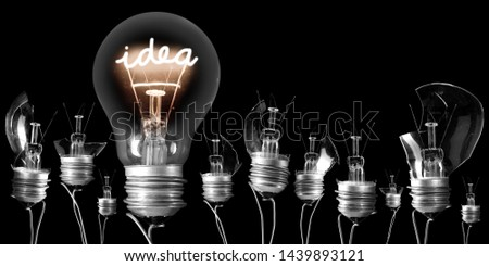 Group of proken light bulbs and shining one of them with fiber in IDEA shape isolated on black background; concept of Idea, Innovation and Success #1439893121