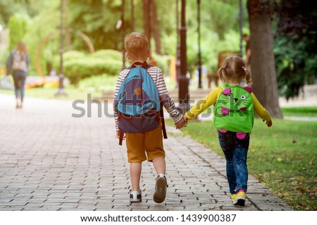 Back to school. Happy children ready for primary school. Pupil on first day of classes. Boy and girl in glasses with backpack and book on backyard. Education for kindergarten and preschool kids. #1439900387