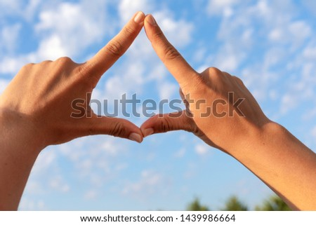 Close up picture of female hands showing a triangle , blue cloudy sky in the background
