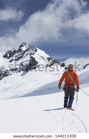 Rear view of a male hiker connected to safety line in snowy mountains #144013300