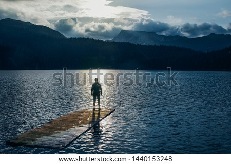 Silhouette man standing on the wooden raft on the blue lake. Cloudy mountain in the back with the evening light in nature landscape. Reflexion on the raft. Black Lake, Montenegro, Durmitor #1440153248