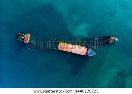 Aerial drone view of sunken cargo ship or tug boat near seaside. Shipwreck vessel with nose of ship above sea water, toned #1440170723
