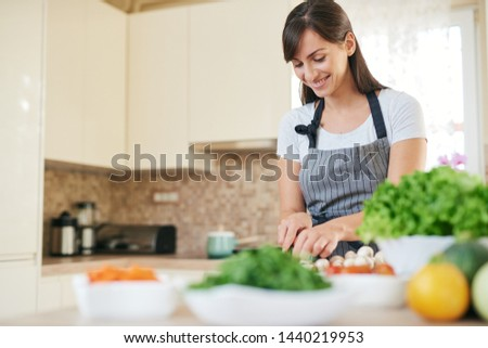Beautiful smiling dedicated Caucasian brunette in apron standing in kitchen and chopping mushrooms. On table are lots of vegetables. Cooking at home concept. #1440219953