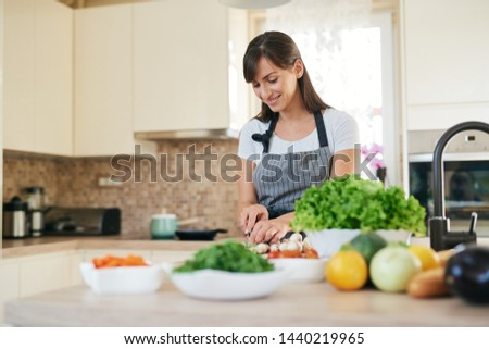 Beautiful smiling dedicated Caucasian brunette in apron standing in kitchen and chopping mushrooms. On table are lots of vegetables. Cooking at home concept. #1440219965