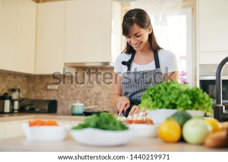Beautiful smiling dedicated Caucasian brunette in apron standing in kitchen and chopping mushrooms. On table are lots of vegetables. Cooking at home concept. #1440219971