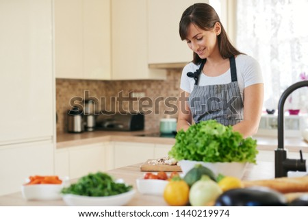 Beautiful smiling dedicated Caucasian brunette in apron standing in kitchen and chopping mushrooms. On table are lots of vegetables. Cooking at home concept. #1440219974