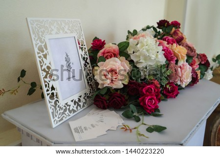 """A bouquet of flowers from roses for the wedding ceremony lies on the table, next is a white photo frame with invitation cards. Translation of the text in the photo frame """"Weddings and flowers""""."""