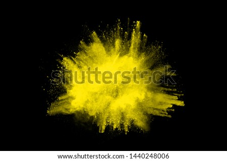 Freeze motion of yellow dust explosion isolated on black background. #1440248006