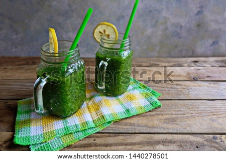 Green home-made smoothies in two glass jars stand on a wooden table on a checkered napkin. ingredients-lemon, spinach, kiwi, broccoli. Healthy food concept, detox, green diet, vegan, keto. Copy space/ #1440278501