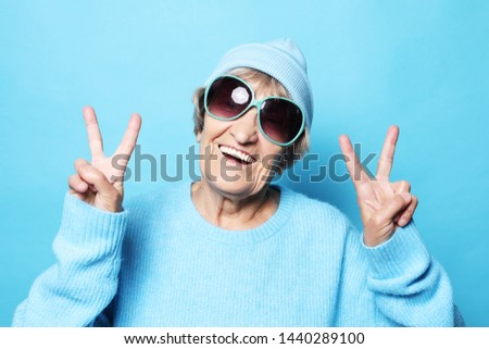 Funny old lady wearing blue sweater, hat and sunglasses showing victory sign. Isolated on blue background. #1440289100