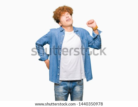 Young handsome man with afro hair wearing denim jacket stretching back, tired and relaxed, sleepy and yawning for early morning #1440350978