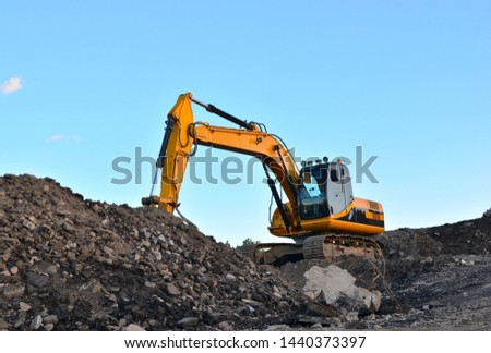 Large tracked excavator works in a gravel pit. Loading of stone and rubble for its processing at a concrete factory into cement for construction work. Cement production factory on mining quarry Royalty-Free Stock Photo #1440373397