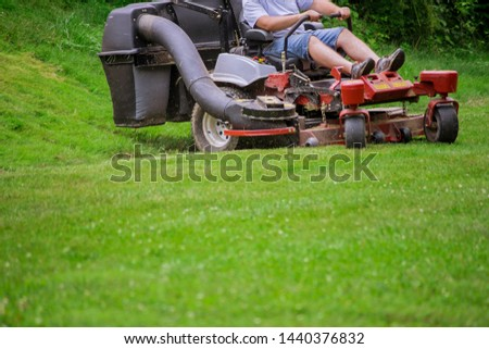 Gardener mowing the lawn lawnmower cutting grass with gardening tools #1440376832