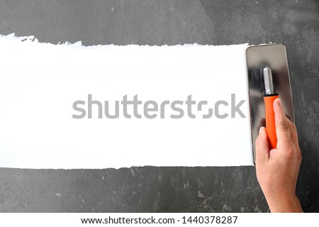Hand with a spatula, the process of applying a layer of putty. Renovation of apartments. Repair the walls. Free space for advertising, text. #1440378287