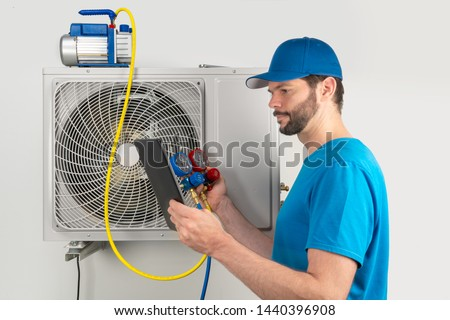 Installation service repair maintenance of an air conditioner outdoor unit, by cryogenist technican worker evacuate the system with vacuum pump manifold gauges tablet in blue shirt and baseball cap #1440396908