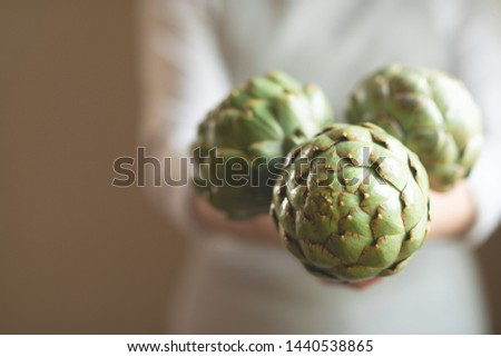 The girl holds in her hands an artichoke with a blur of the background, the concept of proper and dietary nutrition, dottex. horizontal picture