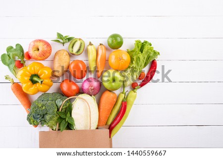 Healthy lifestyle and food concept. Top view paper bag of different fresh vegetables on white wooden background. Flat lay. #1440559667