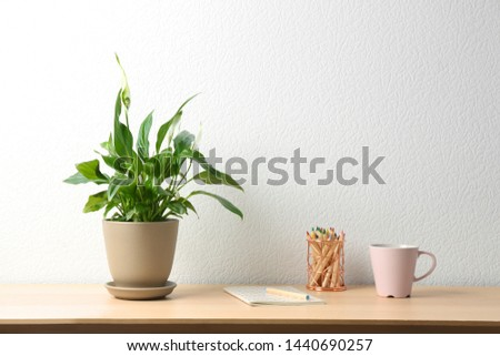Potted peace lily plant, cup and notebook on wooden table near white wall. Space for text #1440690257