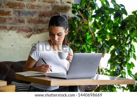 Young businesswoman is working in a cafeteria in her break.Woman taking a break. Enjoying work from coffee shop. Doing Business From coffee shop #1440698669