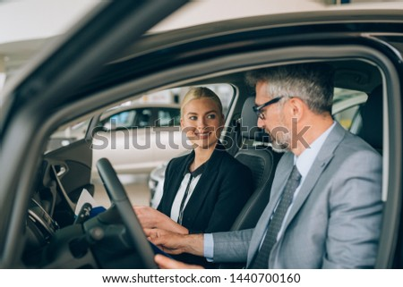 sales woman showing man a new car in car dealership showroom #1440700160