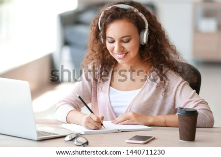 Young African-American student listening to music while preparing for exam #1440711230