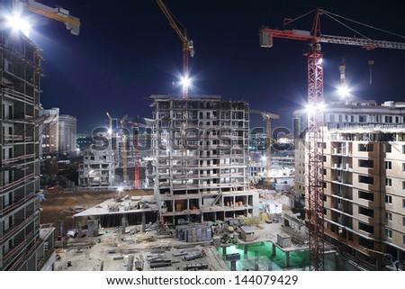Lightening multi-storey buildings under construction and cranes at night. #144079429