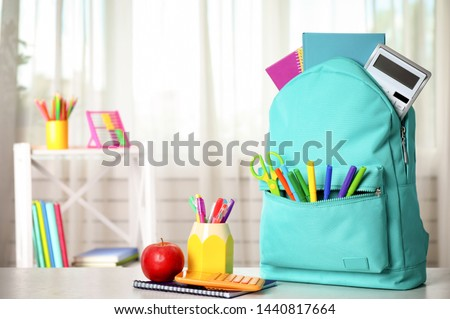 Bright backpack and school stationery on table indoors, space for text Royalty-Free Stock Photo #1440817664