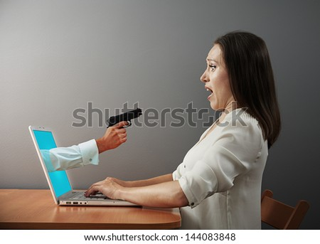 startled woman looking at hand with gun #144083848