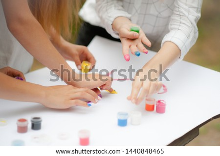 Many hands in gouache paint of different colors in a circle on the background of white paper on paint. Art therapy concept #1440848465