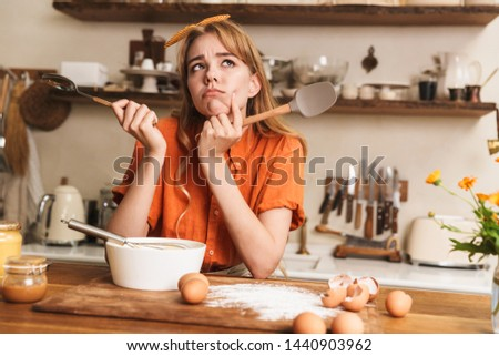 Picture of a thoughtful confused sad young blonde girl chef cooking at the kitchen thinking.
