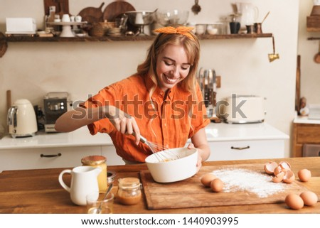 Picture of a happy cheerful smiling young blonde girl chef cooking at the kitchen.